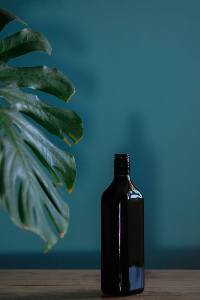 Glass bottle against tropical background