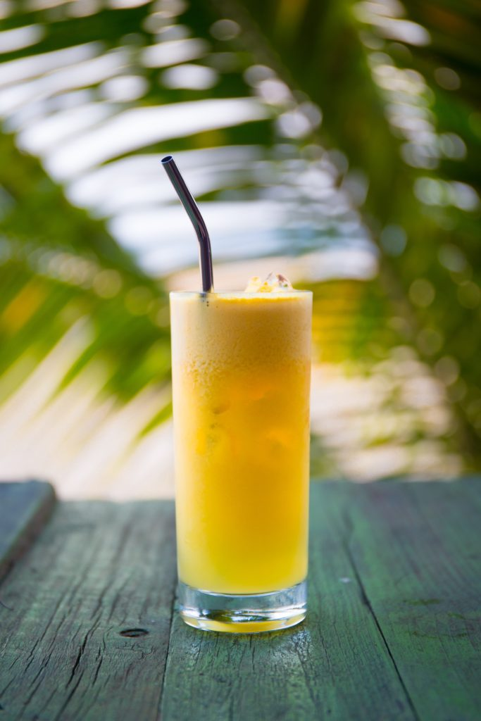 Mango flavored THC Drink on a table in front of palm tree