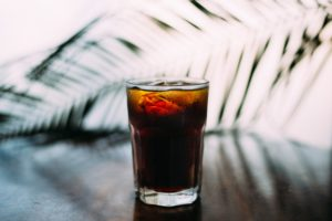 Glass of Soda sitting on a counter with palm frond